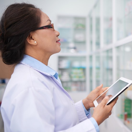 Female pharmacist with iPad looking at shelves