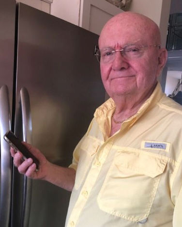 Patient holding a cell phone next to the refrigerator